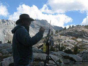 Matt Smith painting on location mountains sky